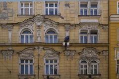 A working man painting the wall of a beautiful house. In praga a man is painting the face of a beautiful and ancient and historic house in the centre of the Royalty Free Stock Image