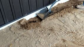 Working man uses flat shovel or spade to move dirt near a house foundation.