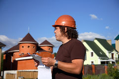 A working man with a plan of construction. Against the backdrop of buildings stock images