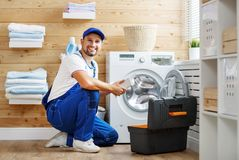 Working man   plumber repairs  washing machine in   laundry. Working man plumber repairs a washing machine in   laundry Royalty Free Stock Images