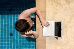 Working man in the pool. A man working with laptop and talking on the phone in the pool. Upper view royalty free stock image