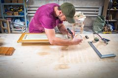 Working man  to protect wooden. A working man in a green cap and t-shirt glues the wooden frame with a double tape to protect himself from paint on a wooden Stock Image
