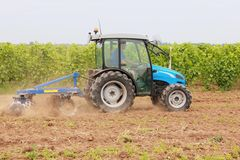 Working man on tractor. Young men drive blue tractor royalty free stock images