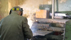 Working in a mask carries out welding of pipes in the manufactory stock video