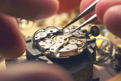 Working On A Mechanical Watch. A watch makers work top. The inside workings of a vintage mechanical watch royalty free stock photography