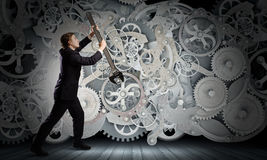 Working mechanism. Young businessman fixing gears mechanism with wrench royalty free stock photography