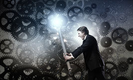 Working mechanism. Young businessman fixing gears mechanism with wrench stock photography