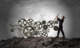 Working mechanism. Young businessman fixing gears mechanism with wrench royalty free stock photos