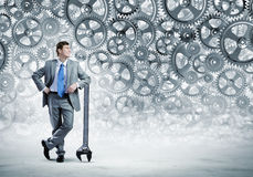 Working mechanism. Young businessman with wrench against mechanism background royalty free stock image