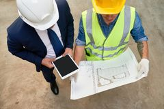 Working Meeting of Foreman and Architect. High angle view of unrecognizable foreman and architect studying blueprint while having working meeting at construction royalty free stock images