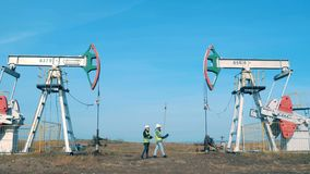Working men check towers, pumping oil. stock video footage