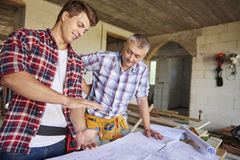 Working men. Younger of carpenters is demonstrating new idea Royalty Free Stock Image
