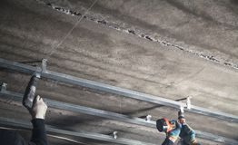 Working with a metal profile of a ceiling construction royalty free stock photo