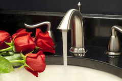 Working mixer tap with a few roses  on a counter Royalty Free Stock Images