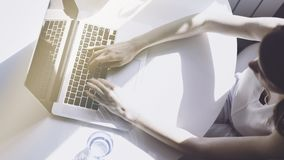 Working moments at coworking.Young woman typing on laptop computer while sitting at the wooden table in light coloured. Living room of modern house Stock Image