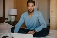 Working moments at home.Happy caucasian coworker man in casual clothes working on laptop at modern apartment. Blurred. Background royalty free stock images