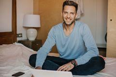 Working moments at home.Happy caucasian coworker man in casual clothes working on laptop at modern apartment. Blurred. Background royalty free stock photo