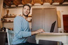 Working moments at home.Young caucasian coworker man in casual clothes working on laptop at modern apartment. Blurred. Background stock photo