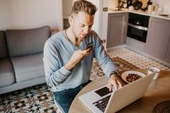 Working moments at home.Young caucasian coworker man in casual clothes working on laptop at modern apartment. Blurred. Background stock photos