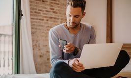 Working moments at home.Young caucasian coworker man in casual clothes working on laptop at modern apartment. Blurred. Background stock images