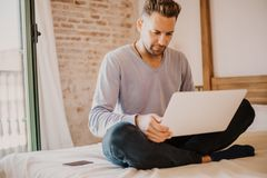 Working moments at home.Young caucasian coworker man in casual clothes working on laptop at modern apartment. Blurred. Background royalty free stock photography