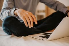 Working moments at home.Young caucasian coworker man in casual clothes working on laptop at modern apartment. Blurred. Background royalty free stock photo