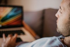 Working moments at home.Young caucasian coworker man in casual clothes working on laptop at sofa at modern apartment. Blurred background royalty free stock images