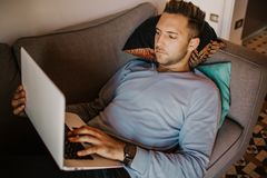 Working moments at home.Young caucasian coworker man in casual clothes working on laptop at sofa at modern apartment. Blurred background stock photos
