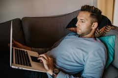 Working moments at home.Young caucasian coworker man in casual clothes working on laptop at sofa at modern apartment. Blurred background stock photography