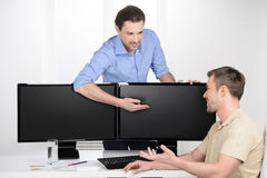 Working moments. Two young businessmen talking about business while one of them pointing computer monitor royalty free stock photography