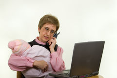 Working Mother 359. Looking at Laptop screen, Talking on the Phone and Holding Baby Royalty Free Stock Images
