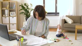 Working mother with baby boy at home office