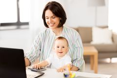 Working mother with baby boy and laptop at home stock photos