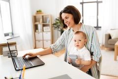 Working mother with baby boy and laptop at home royalty free stock photo