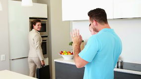Working mother waving goodbye to house husband and baby stock footage