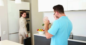 Working mother waving goodbye to house husband and baby stock video footage
