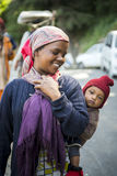 Working mum carry infant on her back feeling happy during her work routine at Shimla district, Himachal Pradesh. Royalty Free Stock Images