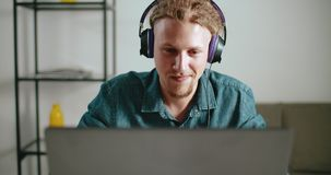 Working with music. Hipster man wears headphones with dreads hair listen to the music while working on laptop stock video footage