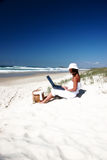 Working on my tan. Woman with laptop on the beach Royalty Free Stock Photos