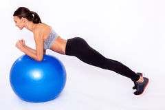 Working my upper body. Full length portrait of a young woman doing exercise with a fitness ball and balancing over white isolated background Stock Photo