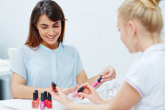 Working in nailcare salon. Beautician looking through nail polishes in nailcare salon Stock Images
