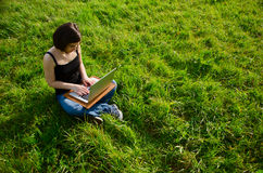 Working in nature. A young woman sitting in a sunny field working on a laptop Stock Photos