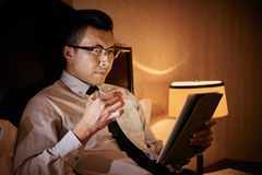 Working at night. Asian businessman lying in bed and reading something on digital tablet at night stock image