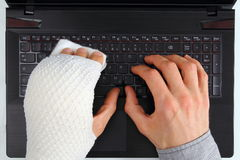 Working on a notebook with hand injury Royalty Free Stock Image
