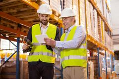 Professional manager talking to his subordinate. Working nuances. Professional warehouse manager holding a tablet while talking to his subordinate Royalty Free Stock Photo