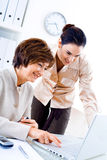 Working in office. Senior businesswoman and young assistant working  at desk in office, smiling Royalty Free Stock Photo