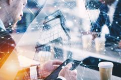 Business man works in office with tablet in the foreground. Concept of teamwork and partnership. double exposure with. Working in office. Business concept with royalty free stock image