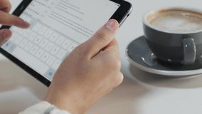 Working in office or coworking space. Close focus on hands typing mail or message on virtual keyboard of portable smart tablet with touch screen, next to cup stock footage