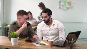 Working in Office. Two good-looking men discussing the ideas using tablet and laptop, slim female colleagues talking about project behind them, concept of stock video footage