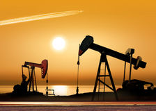 Working oil pumps. Working oil pump in rural place at sunset Royalty Free Stock Image